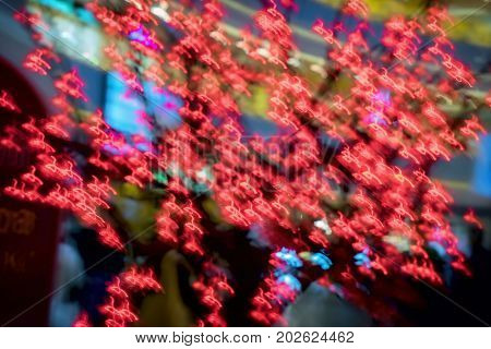 Close-up of red garland, decorative glowing neon sakura. Abstract defocused motion blurred background , backdrop, substrate. Selective focus. Winter holiday, Happy New Year, xmas, Valentine's Day, Spring