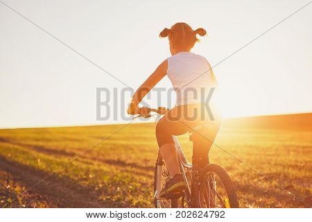 Silhouette of the girl enjoying bike ride at the sunset. Summertime trip in the countryside.