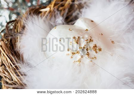 Close-up of christmas decoration from white decorative celluloid mittens with fluffy bird feathers in nest. Festive background , backdrop