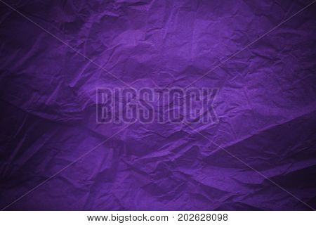 Rough purple vintage paper. Purple crumpled paper texture and background in vintage style. Macro view of wrinkled purple texture made with paper. Purple abstract texture and background for designers.