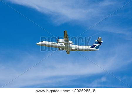 MONTREAL CANADA - AUGUST 28 2017 : WestJet Bombardier Q400 airplane taking off. WestJet Airlines Ltd. is a Canadian airline founded in 1996.