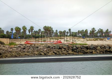 Boulders and rocks separating city beach from harbor straight in San Buenaventura Southern California