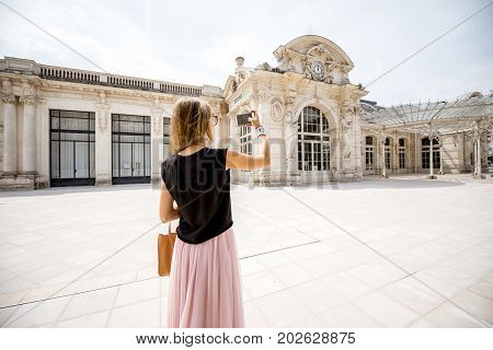 Woman photographing beautiful old Opera building in Vichy city in France