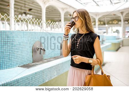 Young woman standing with plastic cup in the old pump room with thermal healing water in Vichy city, France
