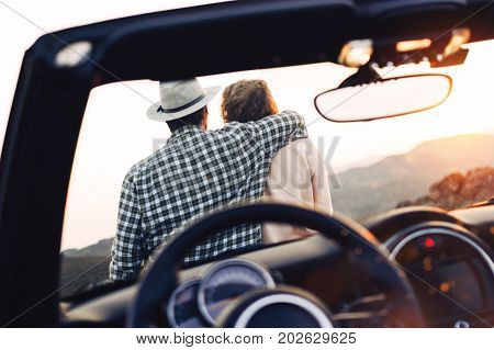 Couple in love hugs and sits on hood of cabriolet. Male and female travelers rest and enjoy sunset near their car