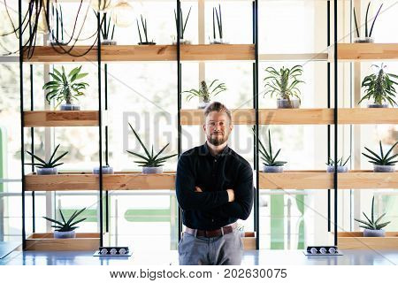 Successful Bearded Young Businessman Standing In His Modern Office