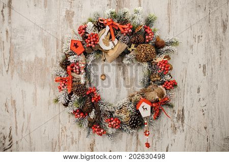 Christmas wreath on a rustic wooden front door close up