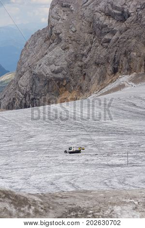 Snow Groomer Snowcat Stands On Dachstein Glacier Near Cable Car