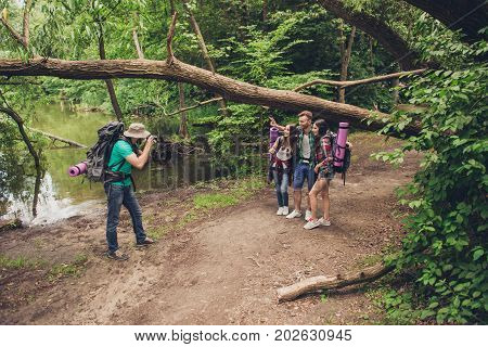 Male Photographer Is Taking Photo Of His Three Friends Near The Lake In The Spring Wood, So Beautifu