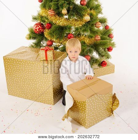 Little boy opening giftbox near christmas tree