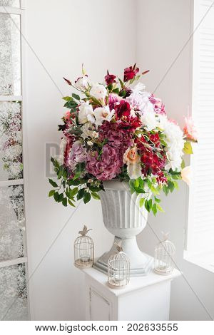 Beautiful flowers in classic white vase. Indoor decoration, gallery. Different colored roses, deep red eustoma, crimson hydrangea in rich blossomed bouquet