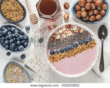 Healthy breakfast. Buckwheat Porridge. Raw buckwheat vegan breakfast smoothie bowl with fresh blueberry, nuts, chia seeds and bee pollen. Clean eating, dieting, detox, vegetarian food concept. Topview