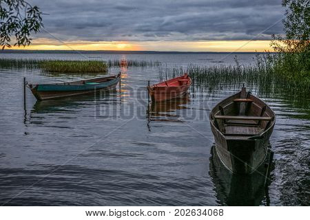 three wooden fishing boats on an autumn decline at the coast of the lake