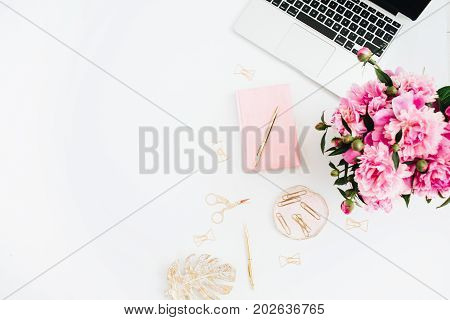 Flat lay home office desk. Woman workspace with laptop pink peonies bouquet. Top view feminine background.