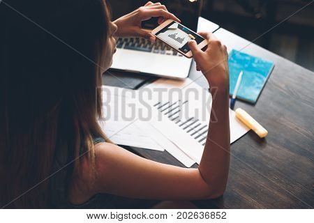 Taking One More Shot. Thoughtful Young Woman Holding A Smart Phone And Looking At It While Sitting I