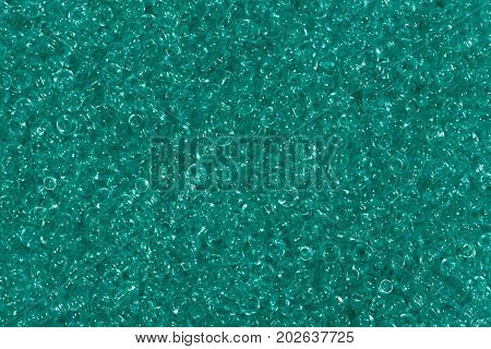 Close up of shiny green seed beads background. High resolution photo.