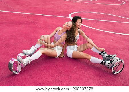 Two Young Girls Sit On The Pink Sports Field. Lough And Fun In Kangoo Jumping Shoes. Fitness Girl In