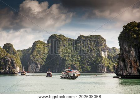 tourist junks in amazing Ha Long bay on a sunny day, UNESCO world heritage sight, Vietnam