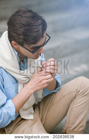 Smoking male closeup. Street style. Young unrecognizable man with bad habits, unhealthy lifestyle, hipster concept