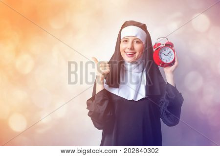 Young Smiling Nun With Red Alarm Clock