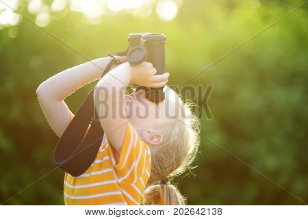 Funny Little Girl Looking Through Binoculars On Sunny Summer Day