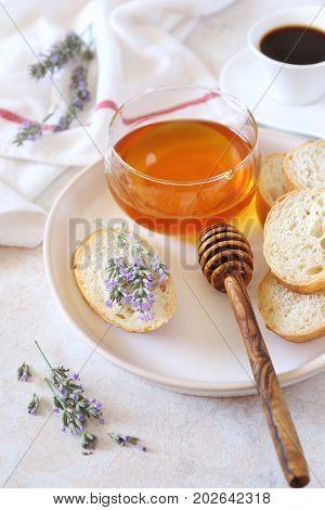 Lavender honey in glass jar flowering lavender and slices of baguette