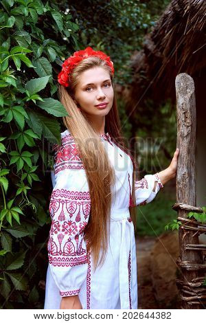 Beautiful slavonic girl with long blond hair and blue eyes with flower crown in white and red embroidered costume.Traditional clothes of Ukrainian region.