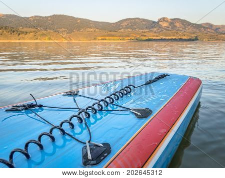 A tail of stand up paddleboard with a leash and bungees on a mountain lake (Horsetooth Reservoir), late summer morning