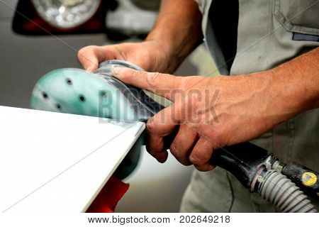 Man in vehicle repair shop sanding a car part with a grinding machine