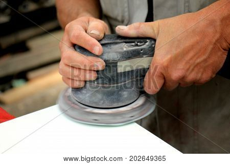 Man in vehicle repair shop sanding a car part with a grinding machine poster