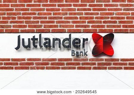 Logstor, Denmark - August 23, 2017: Jutlander Bank logo on a wall. Jutlander Bank is one the largest bank in Denmark measured on working capital
