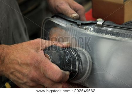 Man polishing a car headlight with sanding machine and fine sandpaper