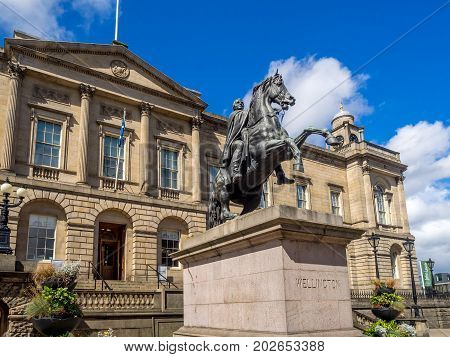 EDINBURGH, SCOTLAND: JULY 26: Duke of Wellington statue on July 26, 2017 in Edinburgh, Scotland. The Scottish archives are located in the background.