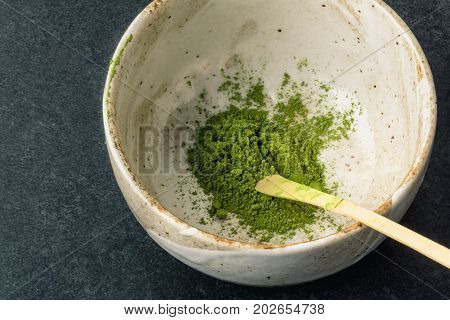 Matcha powder in bowl with Chashaku matcha spoon. Matcha is made of finely ground green tea powder. It's very common in japanese culture. Matcha is healthy due to it's high antioxydant count.