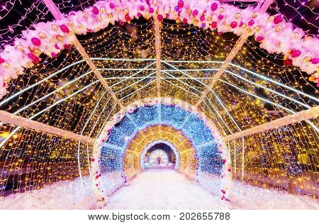Decorated for Christmas and New Year decorative tunnel with Christmas toys and festive lights