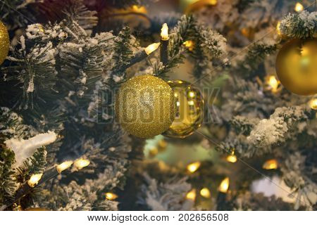 Golden Christmas balls with electric candles in detail