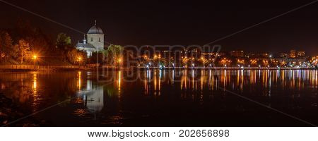 TERNOPIL, UKRAINE - AUGUST 11, 2017: Church of the Exaltation of the Cross over the Ternopil pond. The road from the central part of the city to the neighborhood Druzhba in the night lights.