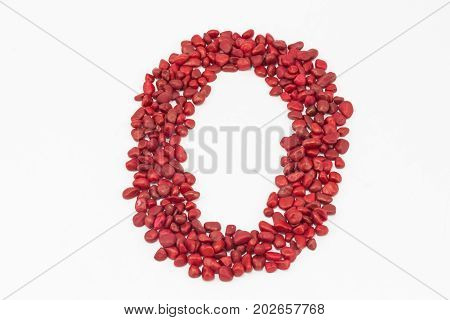 The number zero made by little red stones put one next to the other on a white surface.