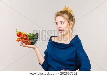 Adult woman do not like to eat vegetables healthy food vegetarian products. Female holding small shopping basket with green red vegetables negative displeased face expression on grey