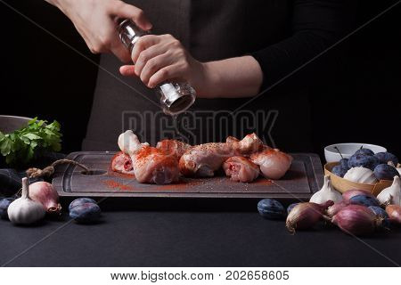 A female chef sprinkles fresh raw chicken drumsticks on a dark background with a mixture of peppers. Nearby lie the ingredients for cooking: shallots, blue plums, garlic pepper, salt and parsley.