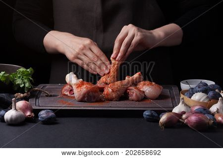 Woman chef rubs salt with fresh raw chicken drumsticks on a dark background. Nearby lie the ingredients for cooking: shallots, blue plums, garlic pepper, salt and parsley.