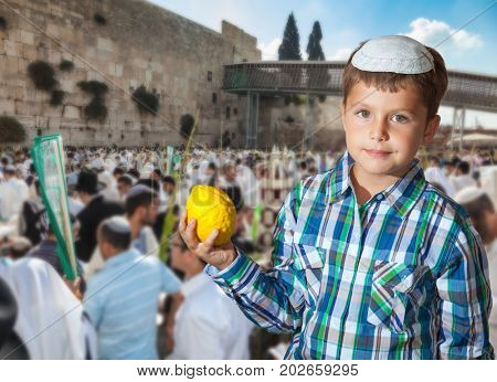 Beautiful Jewish boy with green eyes, in a skullcap, with citrus in his hand. Autumn Jewish holiday Sukkot. The greatest shrine of Judaism is the Western Wall of the Temple