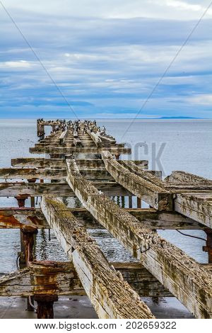 Rusted and destroyed remains of the sea mooring. South of South America. The legendary Strait of Magellan. Cloudy autumn morning. The concept of extreme and active tourism
