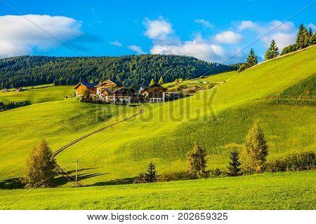 The sun illuminates small picturesque village in Alpine meadows. The Dolomites. The concept of eco-tourism
