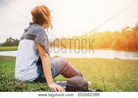 Asian women relax in the holiday. sit relax on a green pasture.