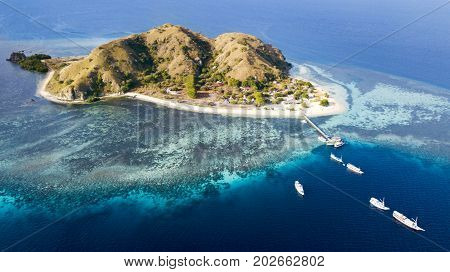 Bird view of tourist boats on the turquoise water while leaving Kanawa island