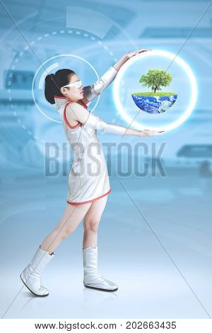 Portrait of futuristic woman standing on the cyberspace while holding a virtual earth with a tree concept of saving earth