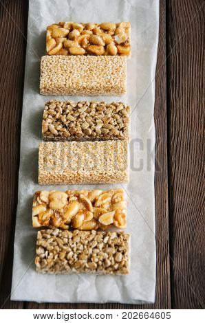 Snacks  - Mix Of Energy Bars With Peanut, Sesame And Sunflower Seeds On A Wooden Background
