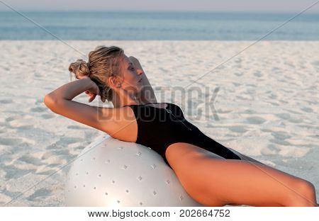 Fitness Woman With Fit Ball On Beach Outdoors.