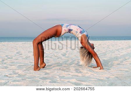 Beautiful Woman Doing Yoga, Urdhva Dhanurasana Pose On Beach